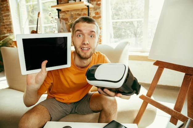 Giovane blogger maschio caucasico con attrezzatura professionale che registra video recensione di occhiali vr a casa. videoblog, vlogging. uomo che mostra tablet e auricolare della realtà virtuale durante lo streaming dal vivo.