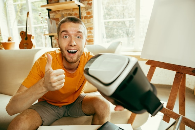 Young caucasian male blogger with professional equipment recording video review of vr glasses at home
