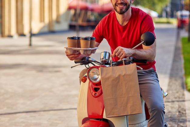 Молодой кавказский курьер-мужчина в красной форме, улыбаясь в камеру, доставляет на скутере четыре кофейных чашки и бумажный пакет с едой. концепция доставки