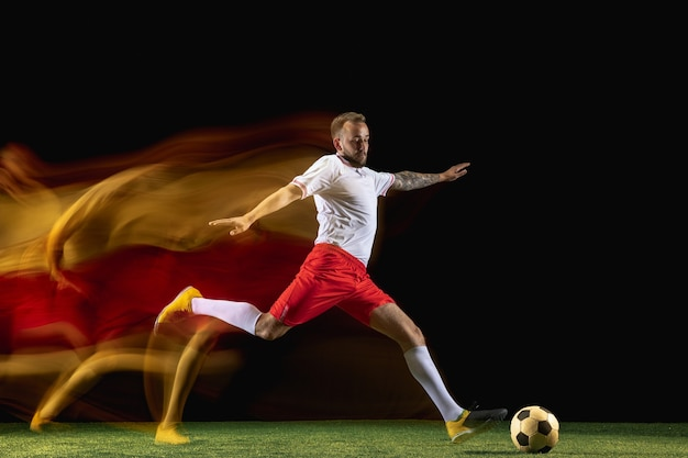 Young caucasian male football or soccer player in sportwear and boots kicking ball
