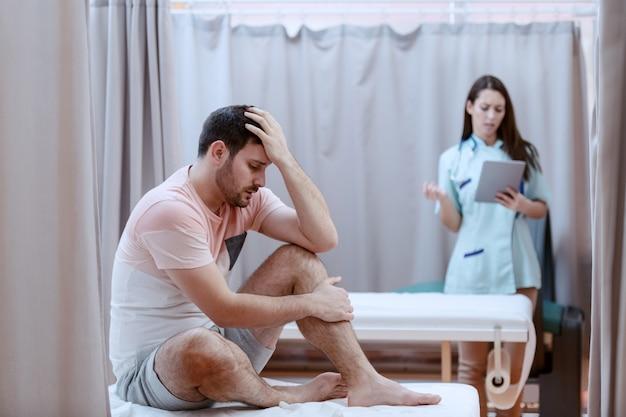 Молодой кавказский мужской пациент сидя на больничной койке и чувствуя боль.