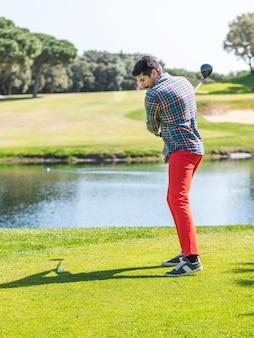 Молодой кавказский мужчина играет в гольф на профессиональном поле для гольфа