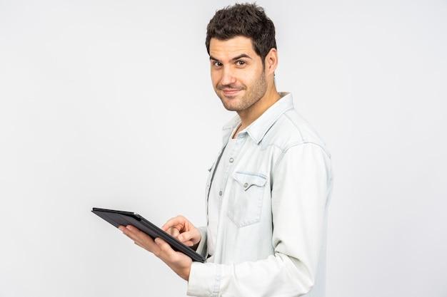 Молодой кавказский мужчина улыбается во время работы над планшетом у белой стены