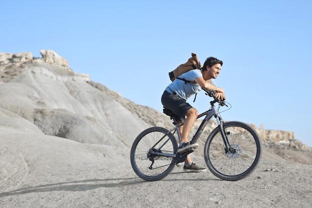 Молодой кавказский мужчина в белой рубашке и рюкзаке катается на велосипеде в безлюдной местности