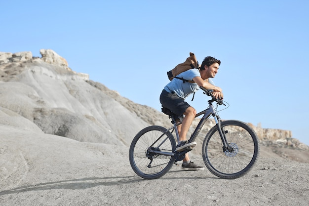 Young caucasian male with a white shirt and a backpack riding a bike in a deserted area