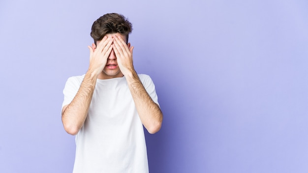 Young caucasian man afraid covering eyes with hands.