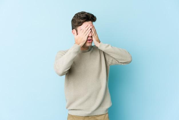 若い白人男性の手で目を覆っていることを恐れています。
