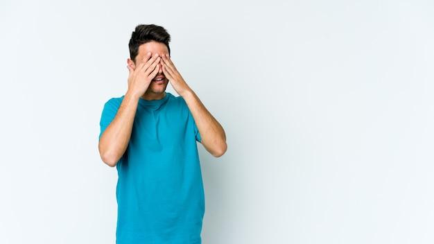 Молодой кавказский человек боится закрывать глаза руками.