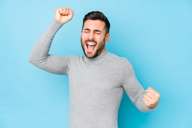 特別な日を祝って分離された青に対して若い白人男がジャンプし、エネルギーで腕を上げる。