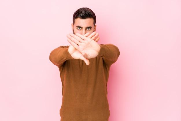 Молодой кавказский человек против розовой стены изолировал делать жест отказа