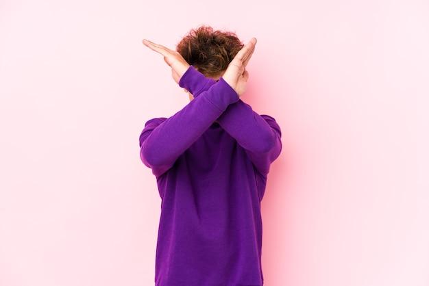 Молодой кавказский человек против розовой стены изолировал, держа скрещенными руками, концепцию отрицания.
