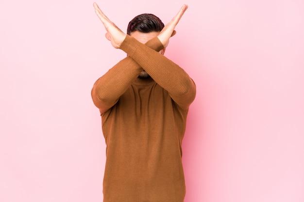 Молодой кавказский человек против розовой стены держа скрещенные руки