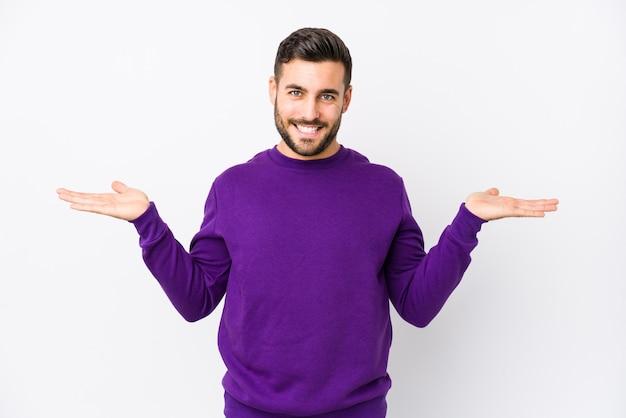 分離した白い背景の若い白人男性は腕でスケールを作る、幸せと自信を感じています。