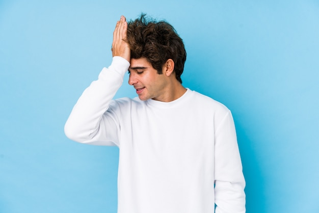 Young caucasian man against a blue wall forgetting something, slapping forehead with palm and closing eyes.