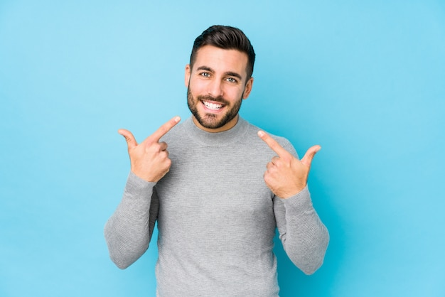 Young caucasian man against a blue wall smiles, pointing fingers at mouth.