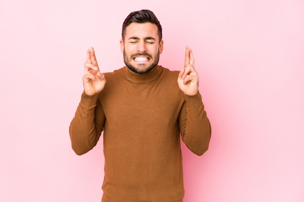 Young caucasian man against a pink background isolated crossing fingers for having luck