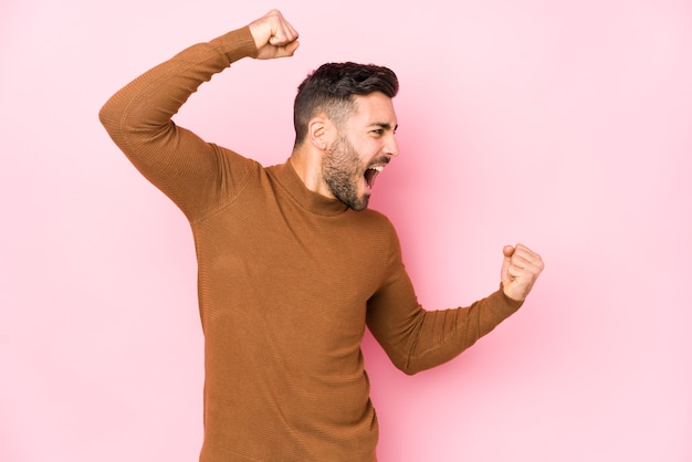 Young caucasian man against a pink background isolated raising fist after a victory, winner concept.