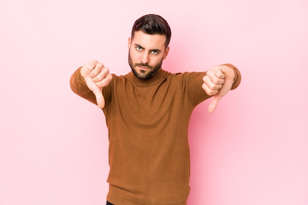 Young caucasian man against a pink isolated showing thumb down and expressing dislike.