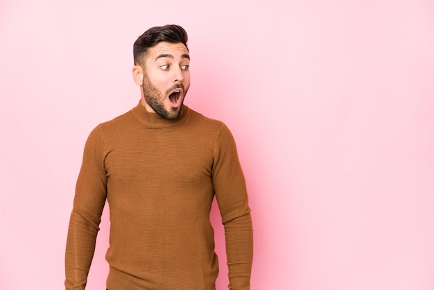 Young caucasian man against a pink wall isolated being shocked because of something she has seen.
