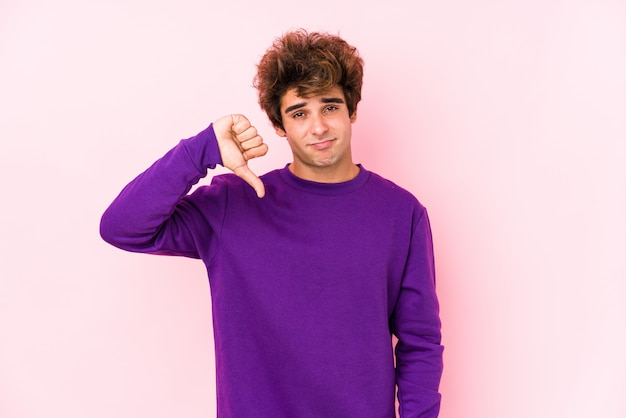 Young caucasian man against a pink wall isolated showing a dislike gesture, thumbs down. disagreement concept.