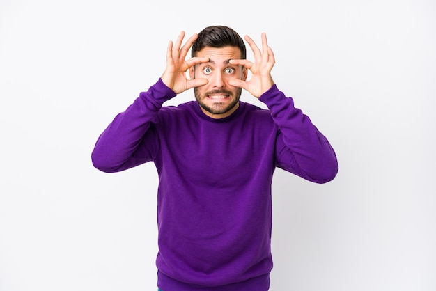 Young caucasian man against a white background isolated keeping eyes opened to find a success opportunity.