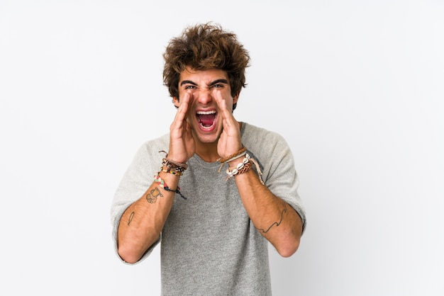 Young caucasian man against a white wall isolated shouting excited to front.