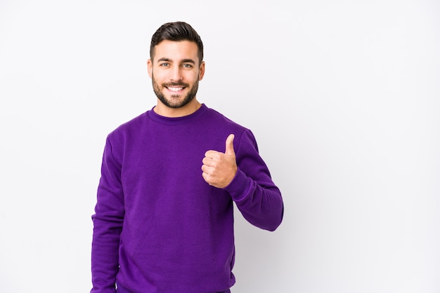 Young caucasian man against a white wall isolated smiling and raising thumb up