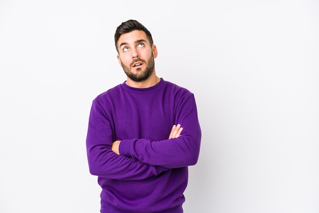 Young caucasian man against a white wall isolated tired of a repetitive task.