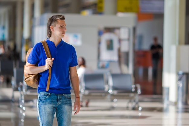 Young caucasian man at airport indoor waiting for boarding