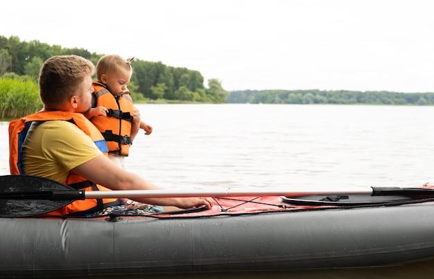 若い白人男性とカヌーカヤックボートの小さな赤ちゃん、ライフジャケット、緑の森の美しい湖のベスト、夏。家族の活動、一緒に余暇を過ごす。水の安全性の概念。コピースペース。