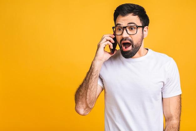 Молодой кавказский человек злой, разочарованный и разъяренный со своим мобильным телефоном, сердитый на обслуживание клиентов. изолированные на желтом фоне.