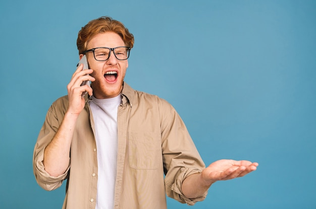 Молодой кавказский человек злой, разочарованный и разъяренный со своим мобильным телефоном, сердитый на обслуживание клиентов