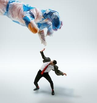 Молодой человек кавказской, избегая большой пластиковой руки на белом фоне.