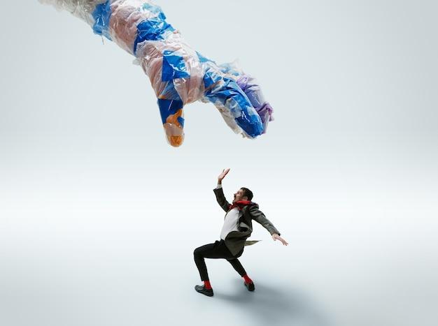 Giovane uomo caucasico evitando la grande mano di plastica su sfondo bianco.