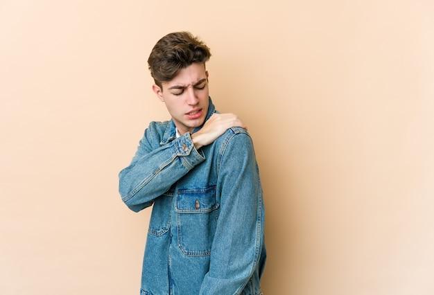 Young caucasian man on beige having a shoulder pain.