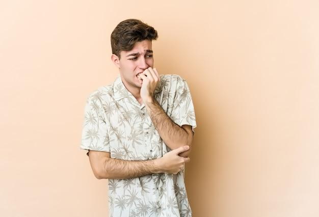 Молодой кавказец кусает ногти, нервничает и очень тревожится.