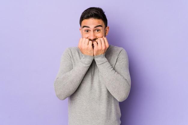 Young caucasian man biting fingernails, nervous and very anxious.