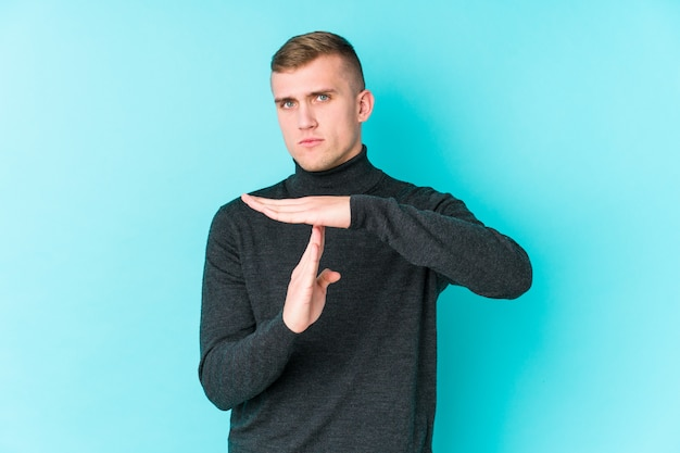 Young caucasian man on a blue background showing a timeout gesture.
