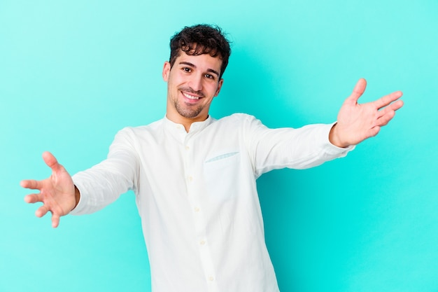 Young caucasian man on blue feels confident giving a hug