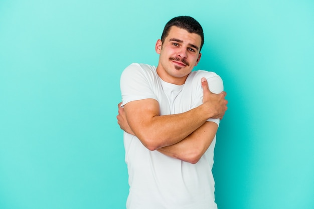Young caucasian man on blue hugs, smiling carefree and happy.