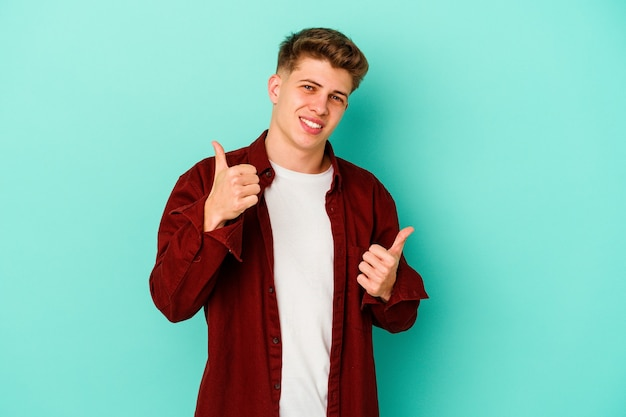 Young caucasian man on blue raising both thumbs up, smiling and confident.