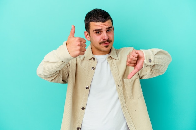 Young caucasian man on blue showing thumbs up and thumbs down, difficult choose concept
