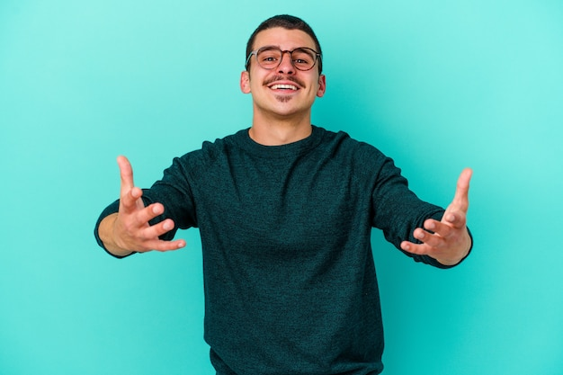 Young caucasian man on blue showing a welcome expression.