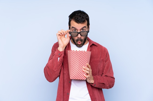 Young caucasian man over blue surprised with 3d glasses and holding a big bucket of popcorns