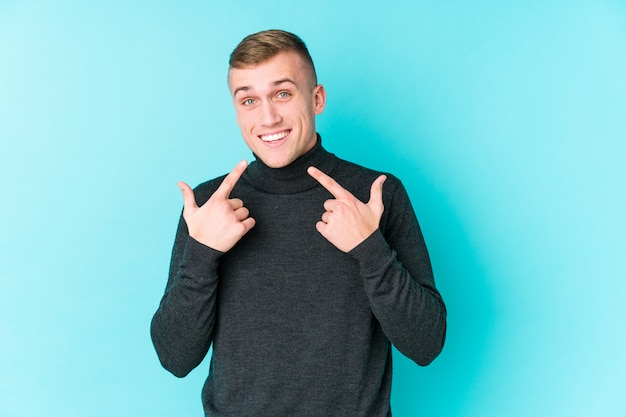 Young caucasian man on a blue wall smiles, pointing fingers at mouth.