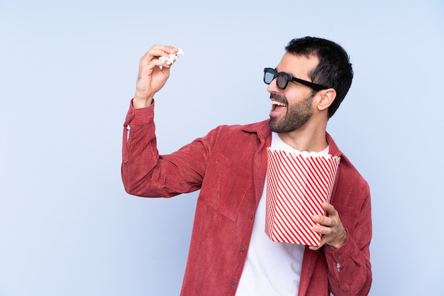 Young caucasian man over blue wall with 3d glasses and holding a big bucket of popcorns