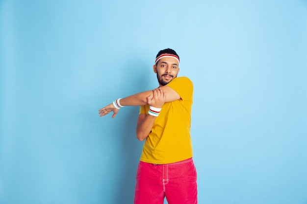 Young caucasian man in bright clothes training on blue background concept of sport, human emotions, facial expression, healthy lifestyle, youth, sales. doing stretching exercises. copyspace.