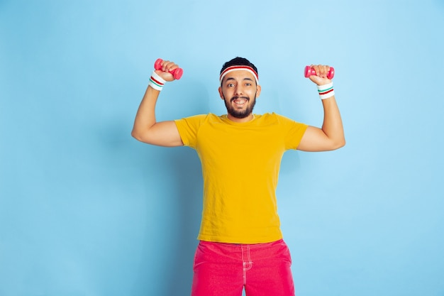 Young caucasian man in bright clothes training on blue background concept of sport, human emotions, facial expression, healthy lifestyle, youth, sales. training with the colorful weights. copyspace.