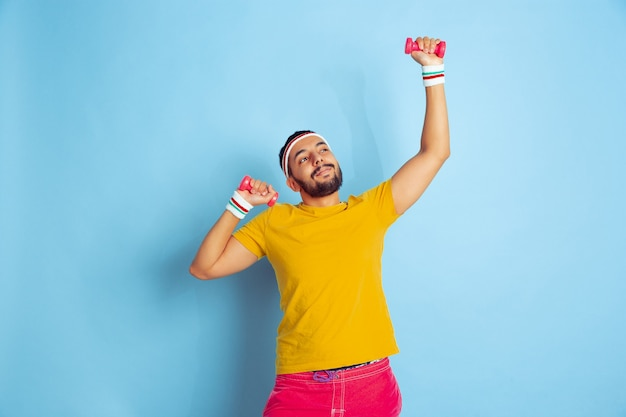 Young caucasian man in bright clothes training on blue background