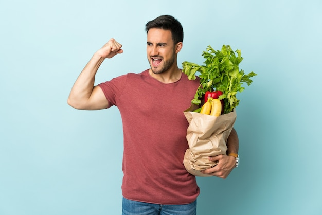 Young caucasian man buying some vegetables isolated on blue celebrating a victory